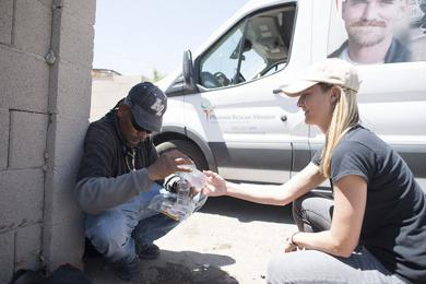 <p>A volunteer gives bottled water to a homeless man as part of the Phoenix Rescue Mission's Code:Red Summer Heat Relief initiative.</p>