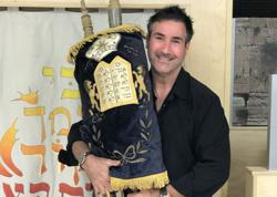 <p>Scott Berger holds the Torah that was made 300 years ago in Morocco.</p>
