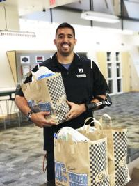 <p>Maxwell Gregory, a personal trainer at the Valley of the Sun Jewish Community Center, picks up an order of produce from North Scottsdale Organics.</p>
