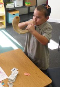 <p>A young student at Torah Day School of Phoenix blows a shofar.</p>