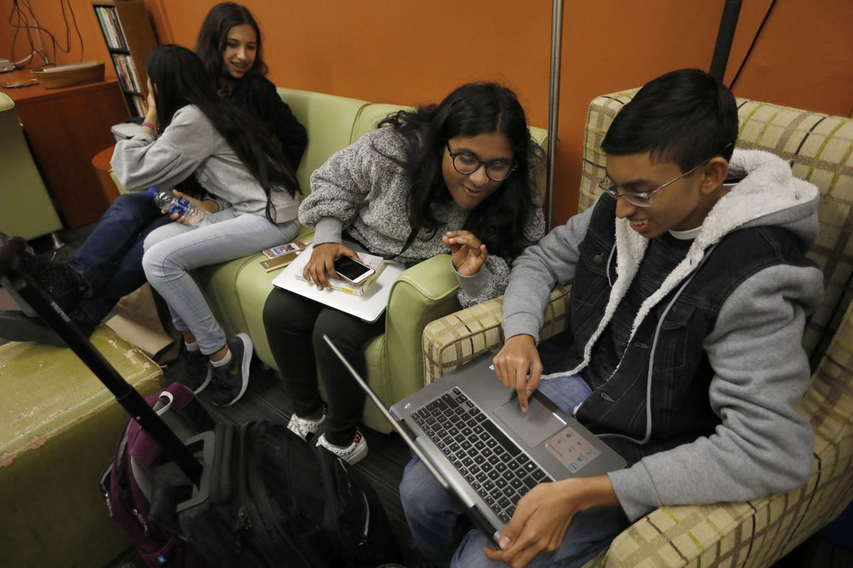 California State University, Los Angeles students Mia Turel, 13, left, Shanti Raminani, 12, middle, Annsana Biju, 13, and Omvikneswer Muralitharan, 15, right, laugh and joke around together after lunch on campus in Los Angeles on January 24, 2019.