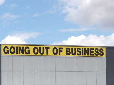Going out of business writing in black on yellow letters on a white cladded industrial building