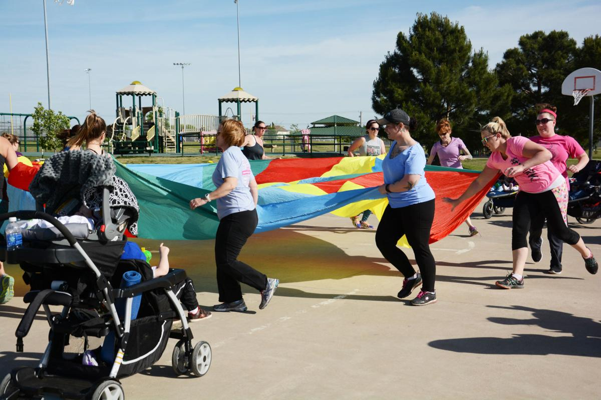 A parachute is used for resistance training during a strength training exercise at a Stroller Stride event at Lions Club Park in Killeen.