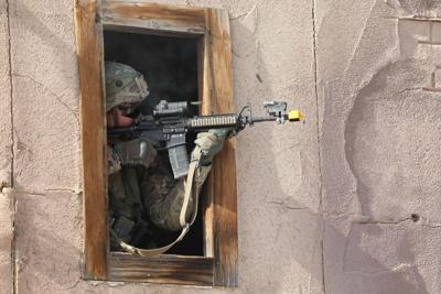 A U.S. Army Soldier assigned to 3rd Squadron, 8th Cavalry Regiment, 3rd Armored Brigade Combat Team, 1st Cavalry Division, Fort Hood, Texas, targets an enemy from a window while clearing a village during Decisive Action Rotation 19-03 at the National Training Center (NTC), Fort Irwin, Calif. Jan. 18, 2019. Decisive Action Rotations at NTC ensure Army Brigade Combat Teams remain versatile, responsive, and consistently available for current and future contingencies. (U.S. Army photo by Spc. Carlos Cameron, Operations Group, National Training Center)
