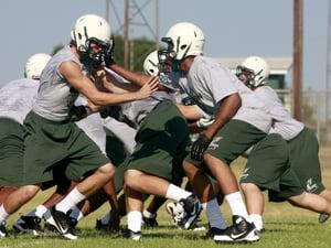 Ellison football players run drills