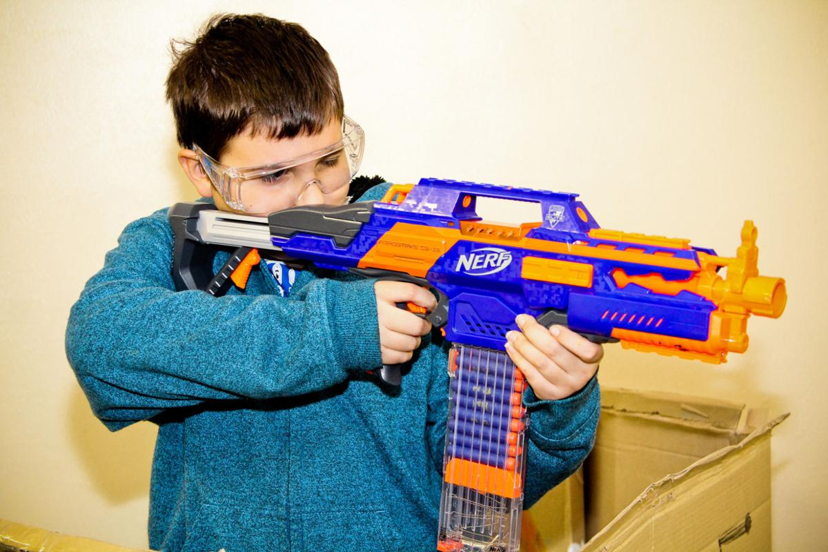Bryant Howe, 12, aims a Nerf gun during the youth group Nerf gun wars at  Robertson Avenue Baptist Church on Saturday, Dec. 27, 2014.