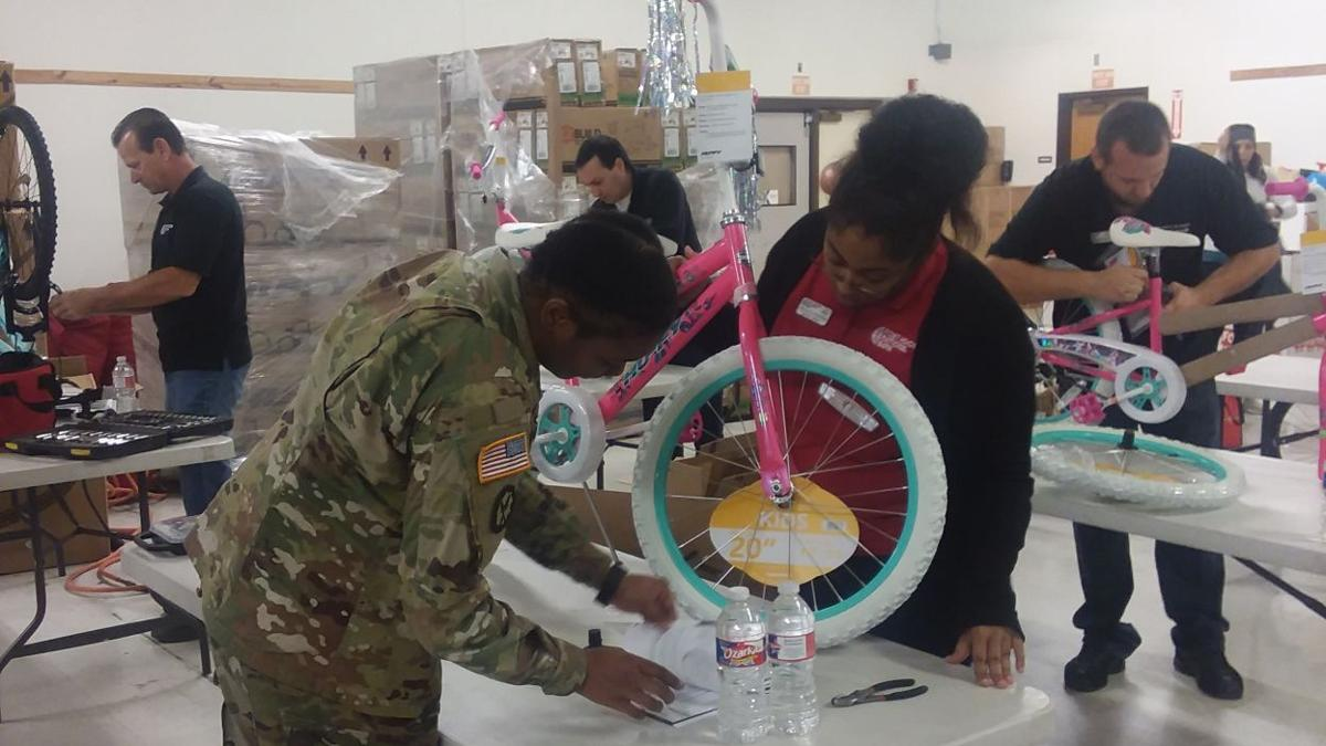 Service members help assemble 1,200 bicycles for Christmas For The Troops