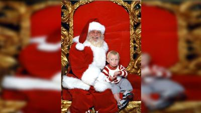 Toddler signs for help while sitting on Santa's lap
