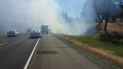 Car overheats, sparking small grass fire along I-90