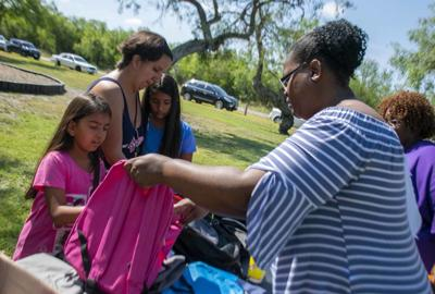 Volunteers hand out backpacks