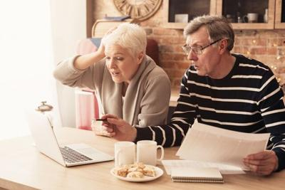 Concerned Senior Couple Using Laptop In Kitchen, Managing Family Budget