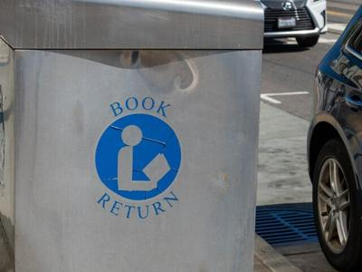Book return symbol and label on outdoor book drop on street at library