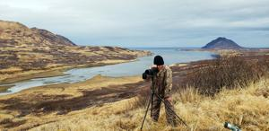 <p>This May, 2019 photo provided by Aleksandr Neverov shows Viacheslav Akimenko using a spotting scope at Sturgeon Lagoon near Kodiak, Alaska, shortly before he died. Akimenko left the men's hunting camp, and Neverov found his friend's body six days later, about a mile from camp with no apparent signs the man was mauled by a bear or harmed himself. (Aleksandr Neverov via AP)</p>