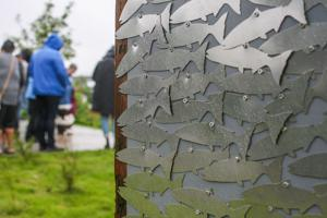<p>A newly installed archway at the park features over 1,200 cut-out salmon, each each representing an Alutiiq Ancestor whose remains have been returned to the archipelago for reburial.</p>