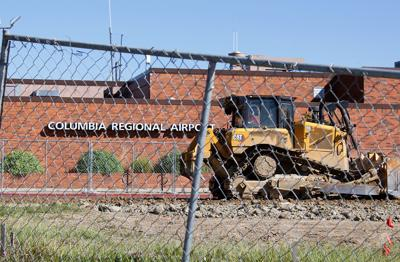 A construction worker tills the ground in front of the Columbia Regional