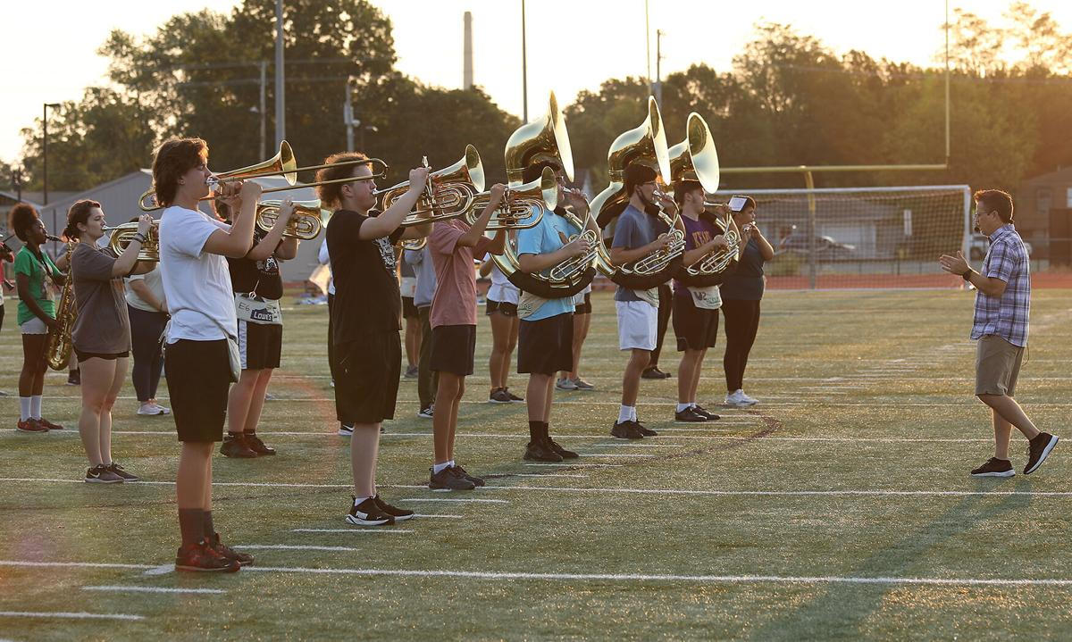 Hickman High School Director of Bands Denis Swope talks to students during a morning rehearsal
