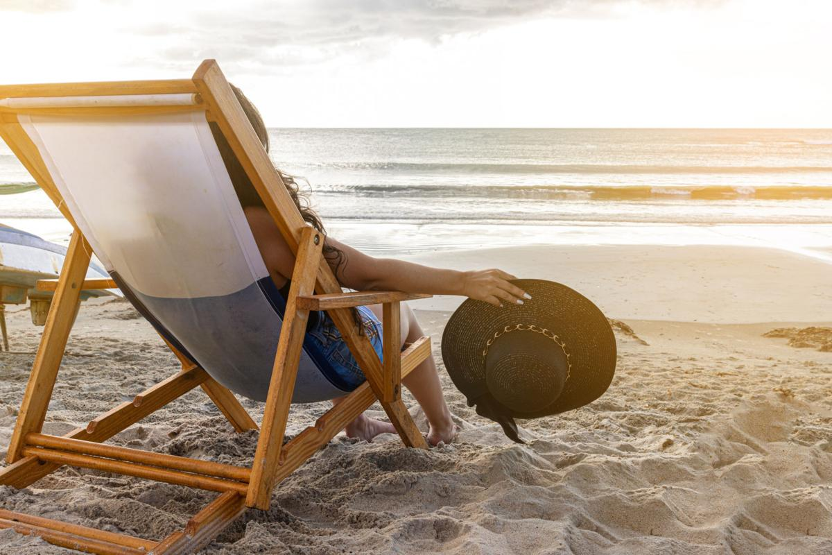 Woman sitting in a beach chair holding her hat