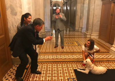 Senator Steve Daines stops to say hello to dog in the capital