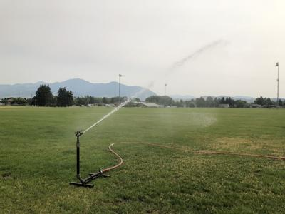A sprinkler watering a lawn at Bozeman High School.