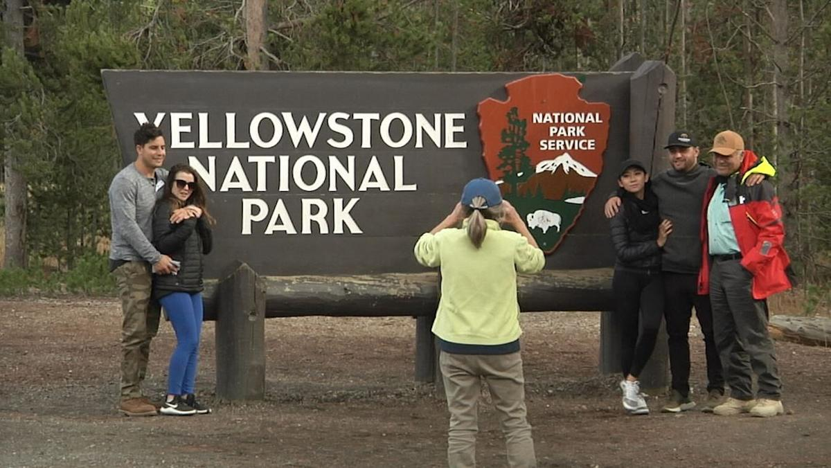 Yellowstone National Park sign with tourists
