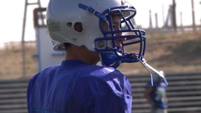 Teen overcomes his body's limitations to join others on the football field