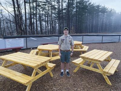 Declan Ulricson proudly stands with the picnic tables