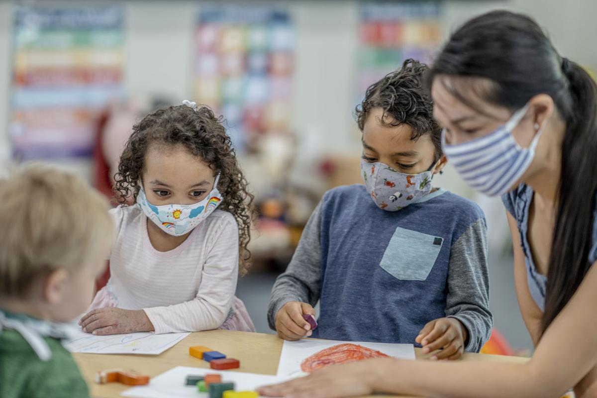 Group of children colouring while wearing masks
