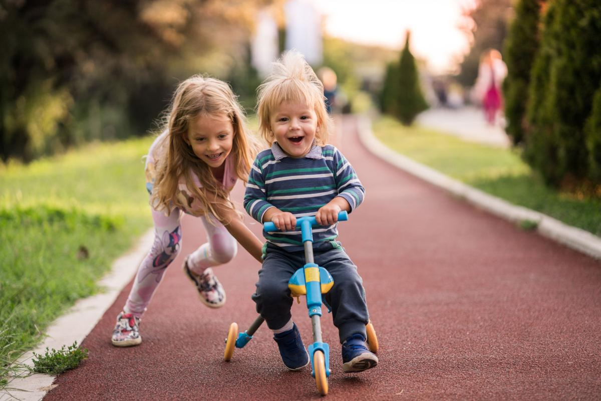 Happy boy having fun on tricycle while his sister is pushing him.