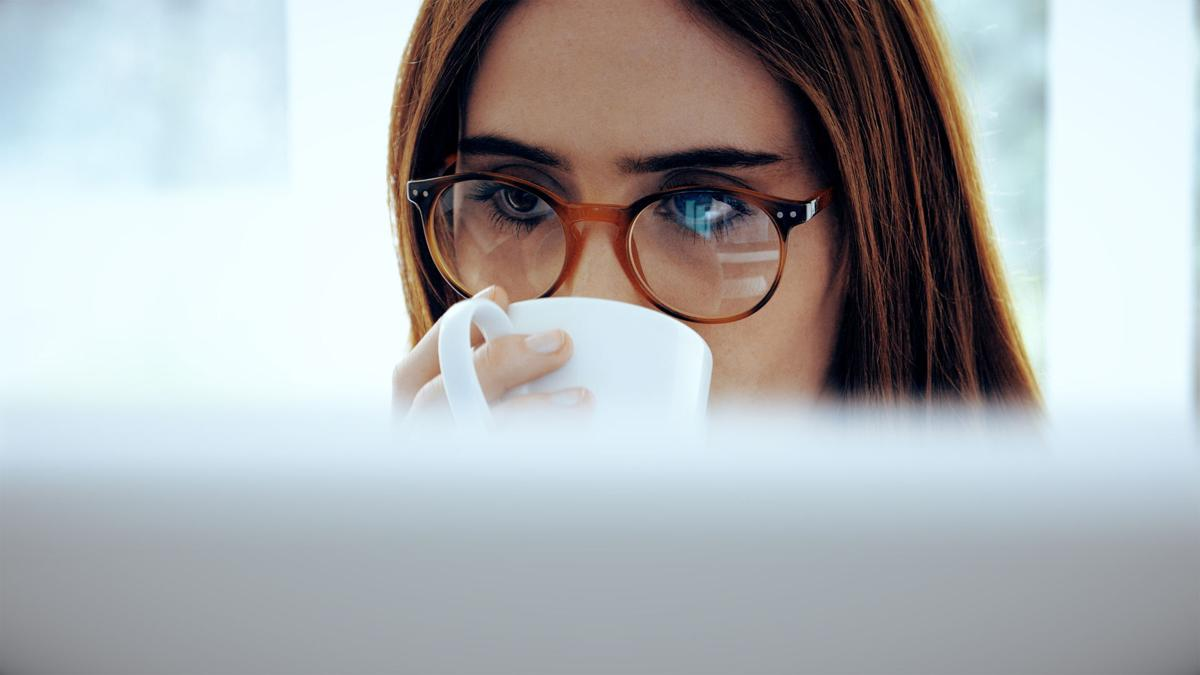 Computer and coffee, woman wearing glasses.