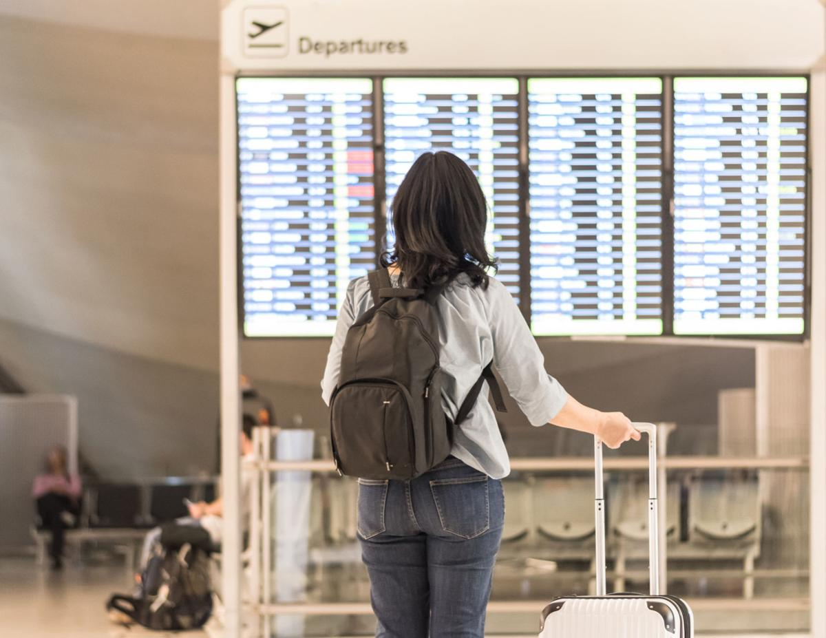 Passenger traveling with luggage and backpack at the flight information board in airport terminal waiting hall area checking time for departure-arrival and delay flight status