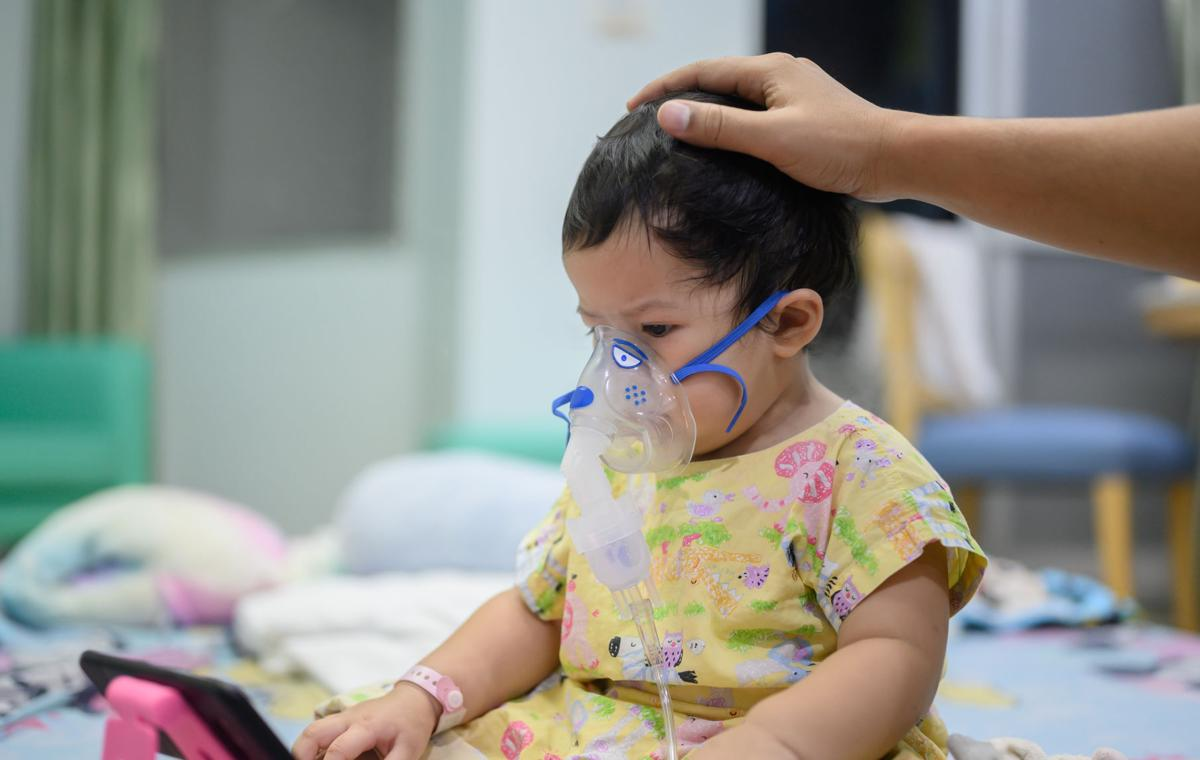 Asian baby was sick as Respiratory Syncytial Virus (RSV) in kid hospital. Thai little girl having inhaler containing medicine for stop coughing and disease flu.