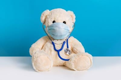 Teddy bear with protective medical mask and stethoscope. Concept of illness, hygiene and virus protection for children
