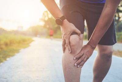 Midsection Of Man Holding Knee While Jogging In Park