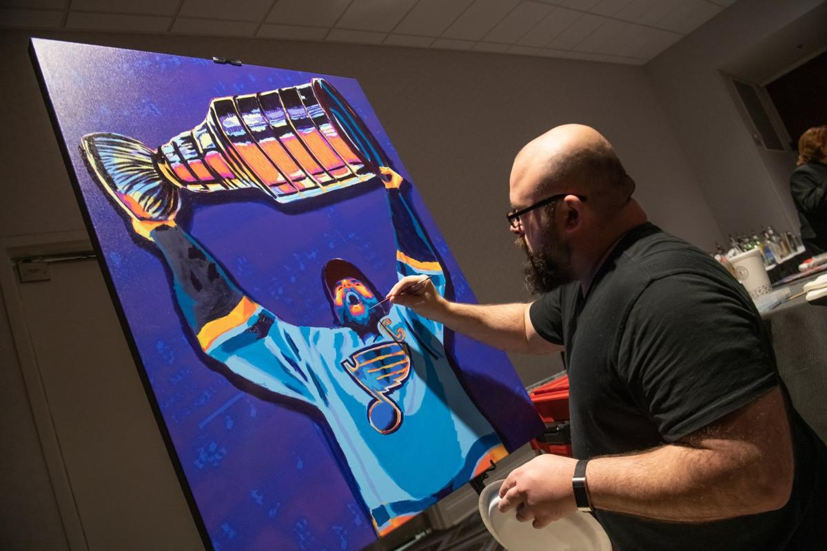 Steven Walden works on a painting of St. Louis Blues captain Alex Pietrangelo