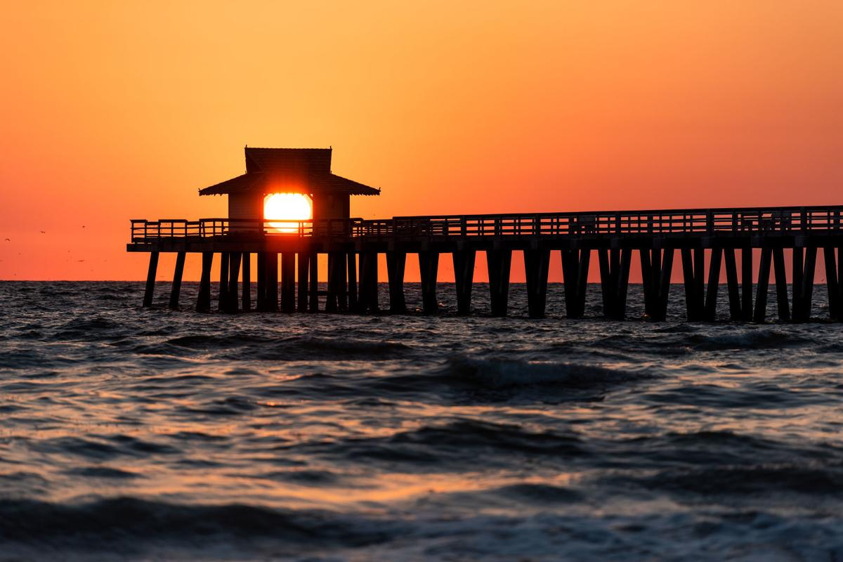 Naples, Florida vibrant orange sunset, in gulf of Mexico with sun peeking in behind Pier wooden jetty, with horizon and dark silhouette ocean waves