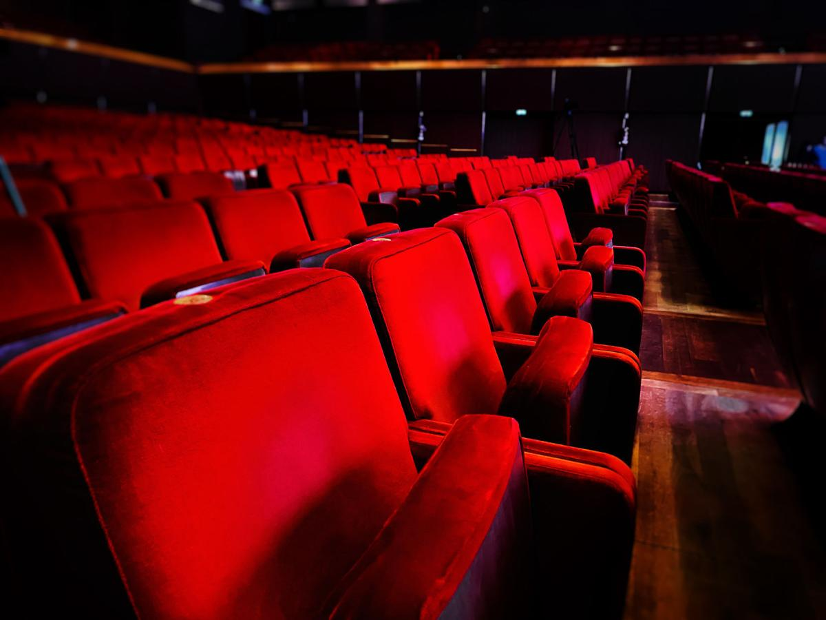 a row of empty red velvet armchairs inside an auditorium.