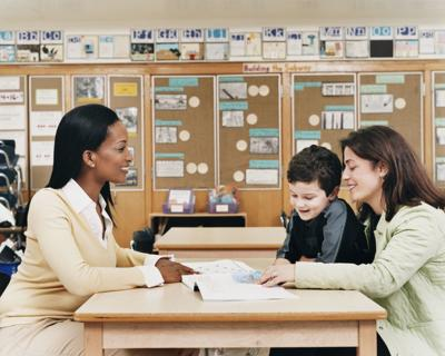 Teacher Sitting at a School Desk Showing a Book to a Parent and Her Son