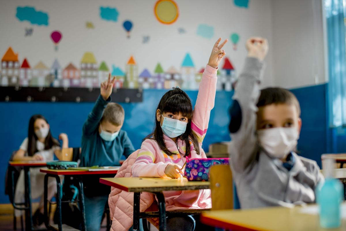 Elementary schoolchildren wearing a protective face masks  in the classroom. Education during epidemic.