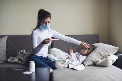 A Mother Measure Temperature On Her Sick Child At Home.