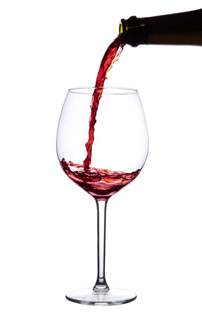 Red wine pouring into wine glass. Pinot noir. Isolated.
