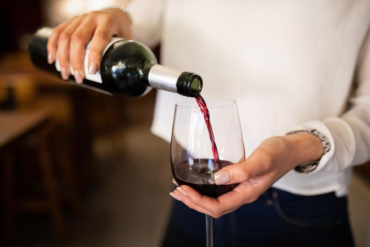 Woman serving red wine in a winery