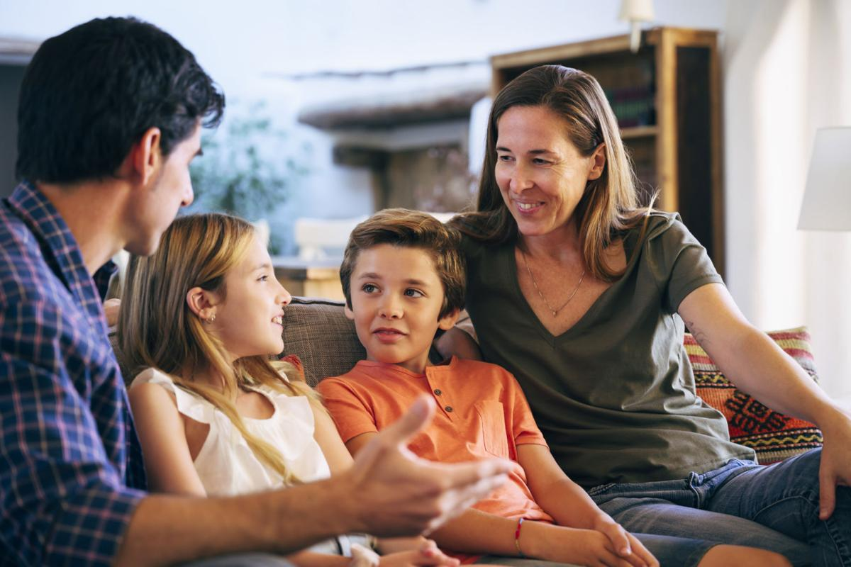 Young Spanish family together on sofa in family home