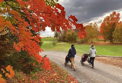 Two golfers pushing their golf carts down a path on a beautiful cool autumn day in Canada