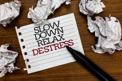 Text sign showing Slow Down Relax De Stress. Conceptual photo Have a break reduce stress levels rest calm Paper lumps laid randomly around white notepad touch black pen on woody floor.