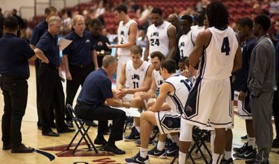 Coach Mike Dunlap discussing strategies with the team during a timeout.