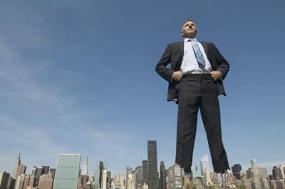 Confident Businessman Giant Towering Over City Skyline