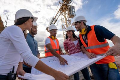 Group of civil engineers looking at a blueprint at a construction site