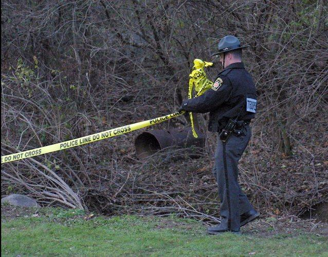 Trooper gathers up crime scene tape