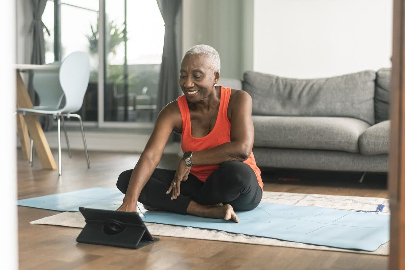Woman sitting on yoga mat with tablet.jpg