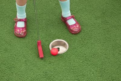 Little Girl Putting at Miniature Golf, looking down at feet